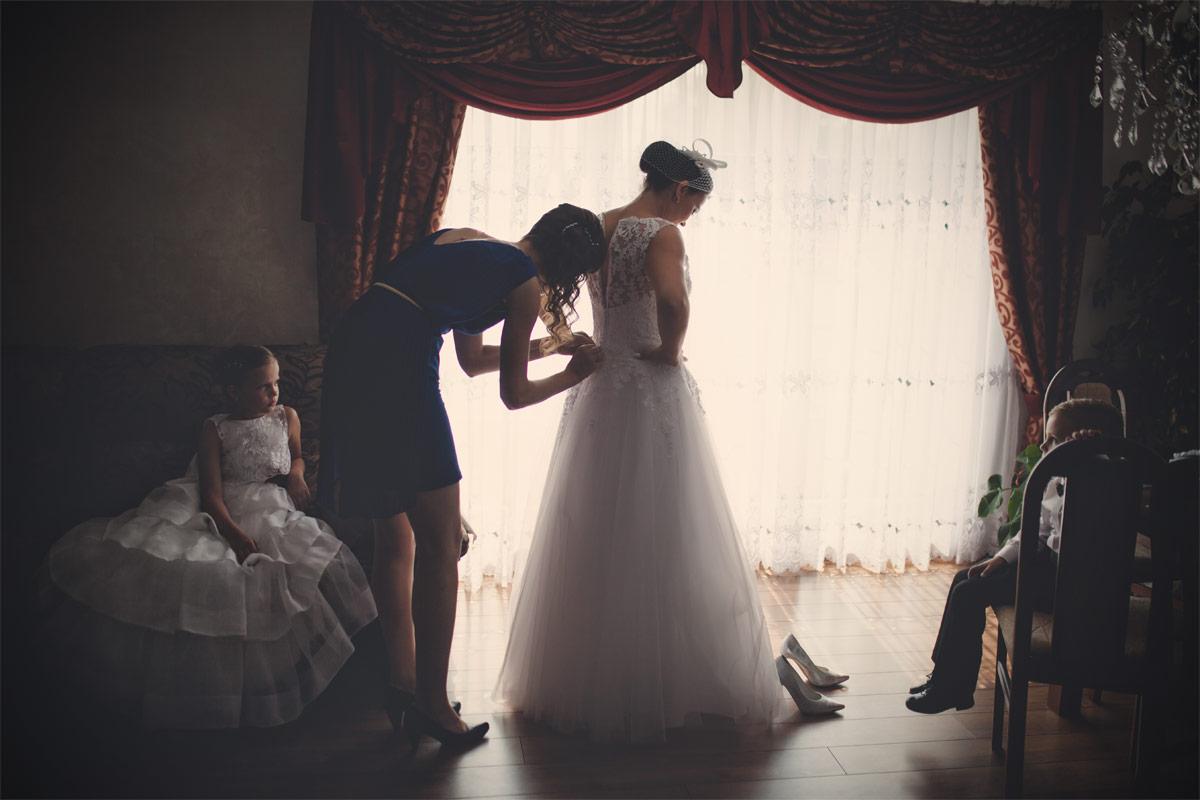 Wesele w Baranowskiej Chacie - zakładanie sukienki ślubnej