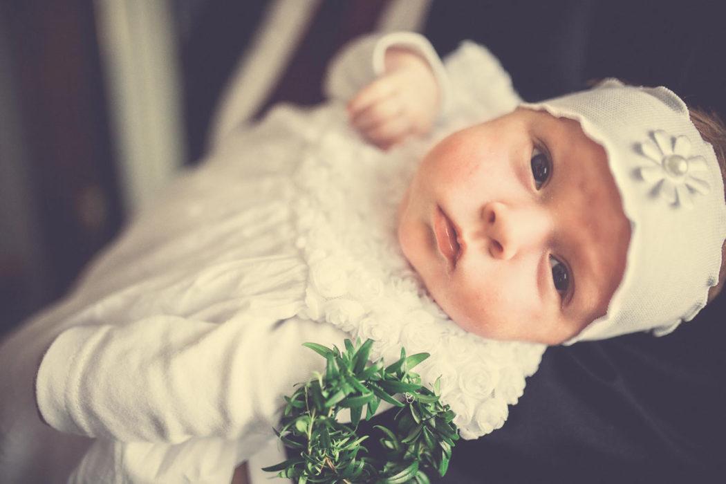 Zdjęcia z chrztu świętego portret dziecka. Na ramionach u ojca.