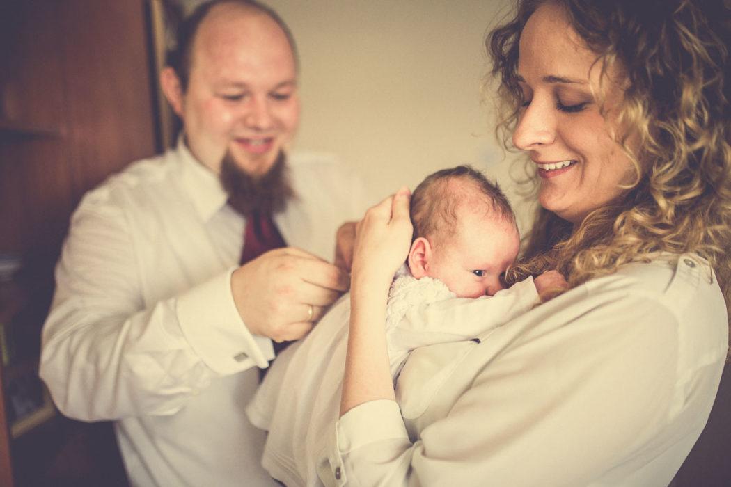Zdjęcia z chrztu świętego przygotowania w domu. Dziecko z rodzicami.