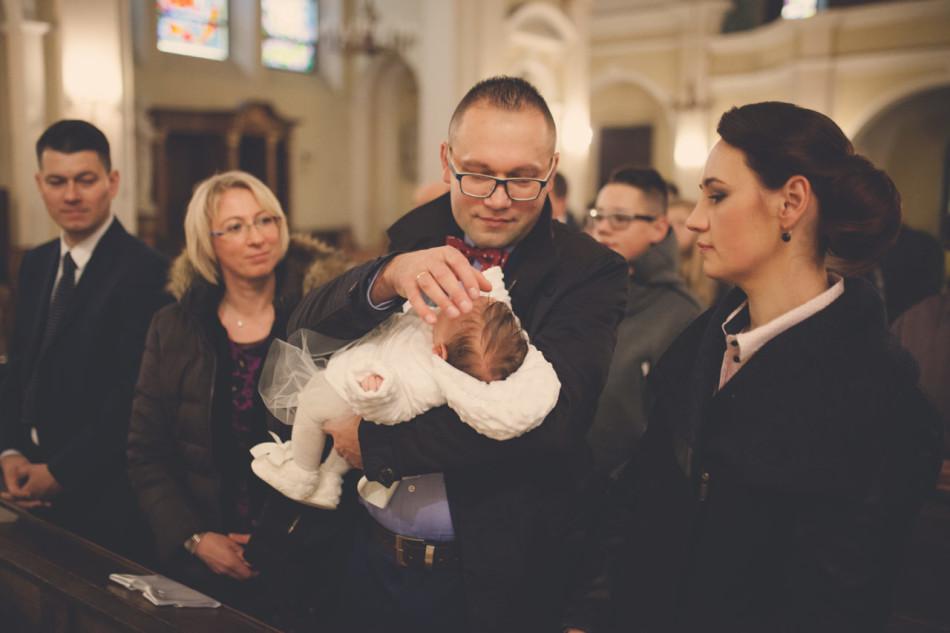 Zdjęcia z chrztu w kościele ojciec błogosławi dziecko