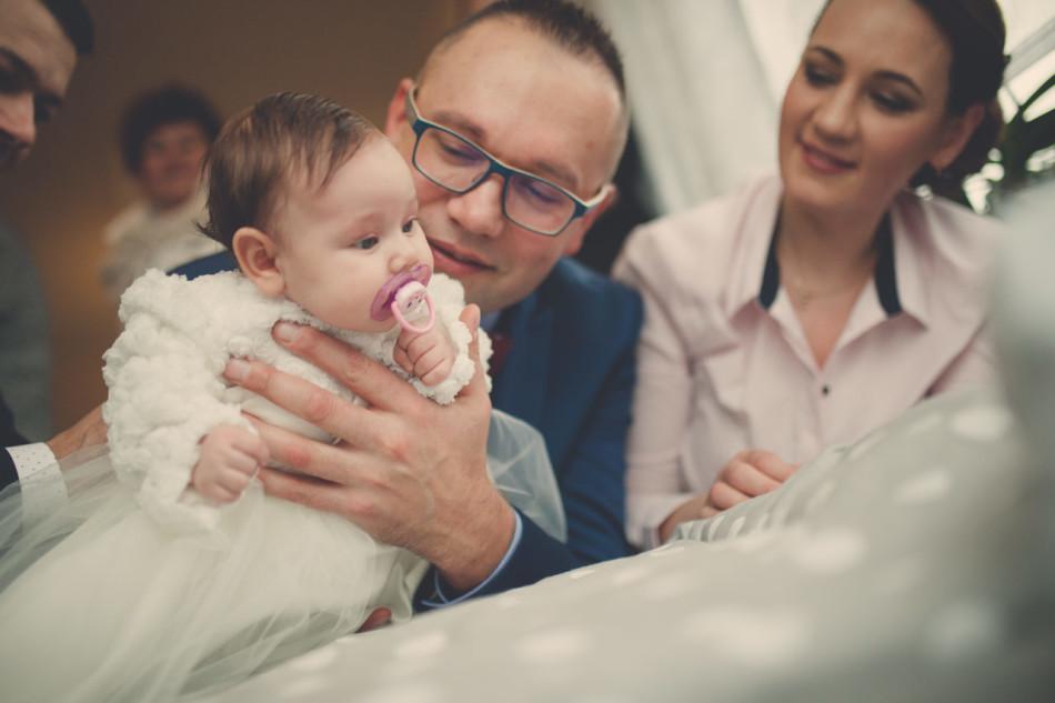 Zdjęcia z chrztu córka z ojcem w ramionach w trakcie przygotowań do ceremonii