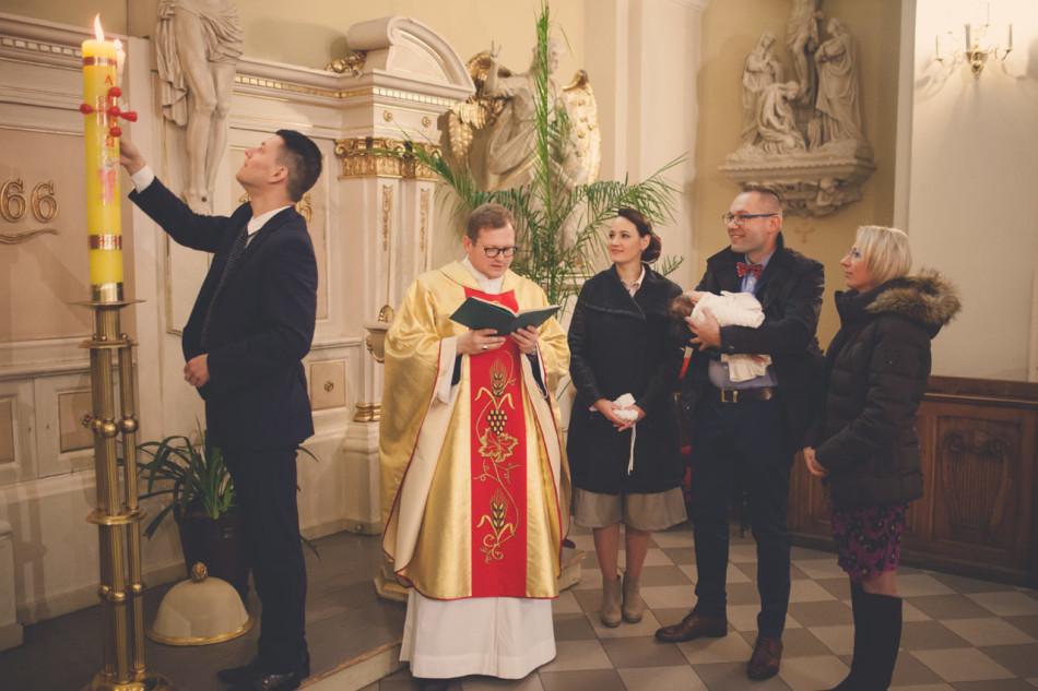 Zdjęcia z chrztu w kościele odpalanie świecy od paschału przez chrzestnego