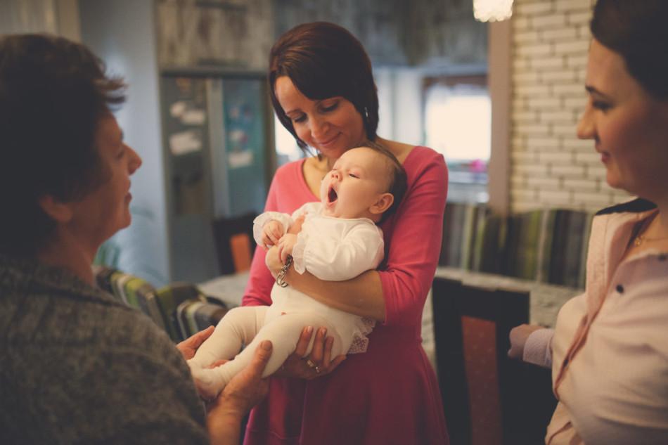 Zdjęcia z chrztu w domu na ramionach osób z rodziny