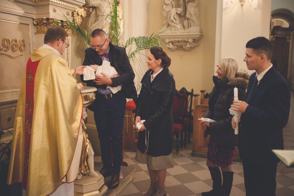 Zdjęcia z chrztu w kościele w trakcie udzielania sakramentu