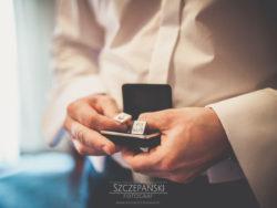 Detale ślubne Pan Młody wyjmujący spinki z pudełka