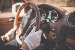 Detale ślubne dłonie szofera ślubnego w rękawiczkach ułożone na kierownicy