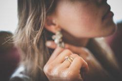 Detale ślubne dłoń Pani Młodej zakładającej kolczyki
