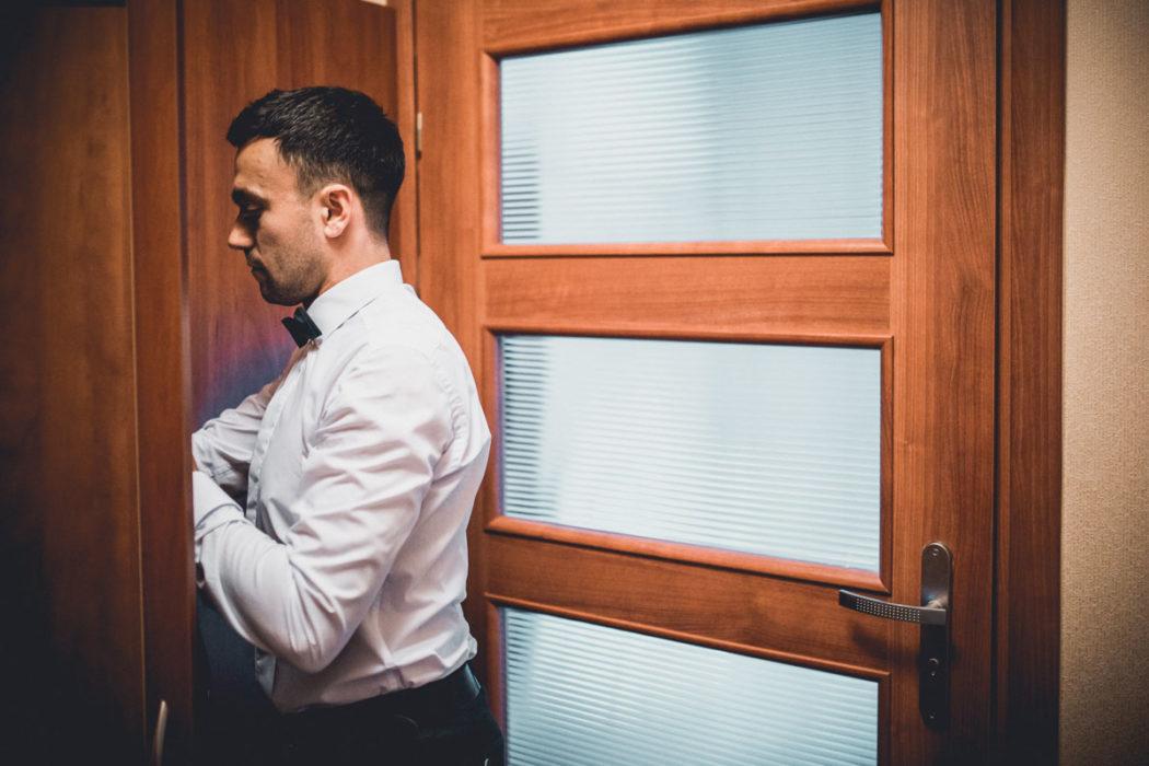 Pan Młody ubiera się w pokoju hotelowym w Hotelu Borowianka