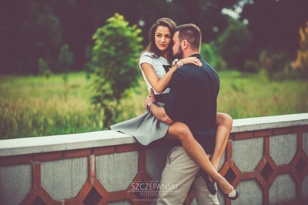 Sesja narzeczeńska - narzeczony przytula dziewczynę na mostku