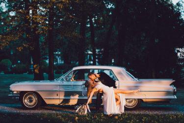 Para młoda całuje się na tle weselnego samochodu. Pytania do fotografa