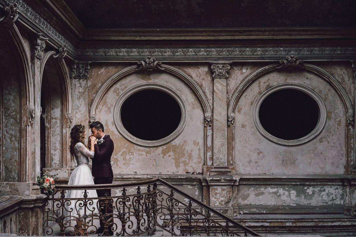 Pan młody całuje w dłonie żonę stojąc na balkonie we wnętrzach Pałacu Karowiarki