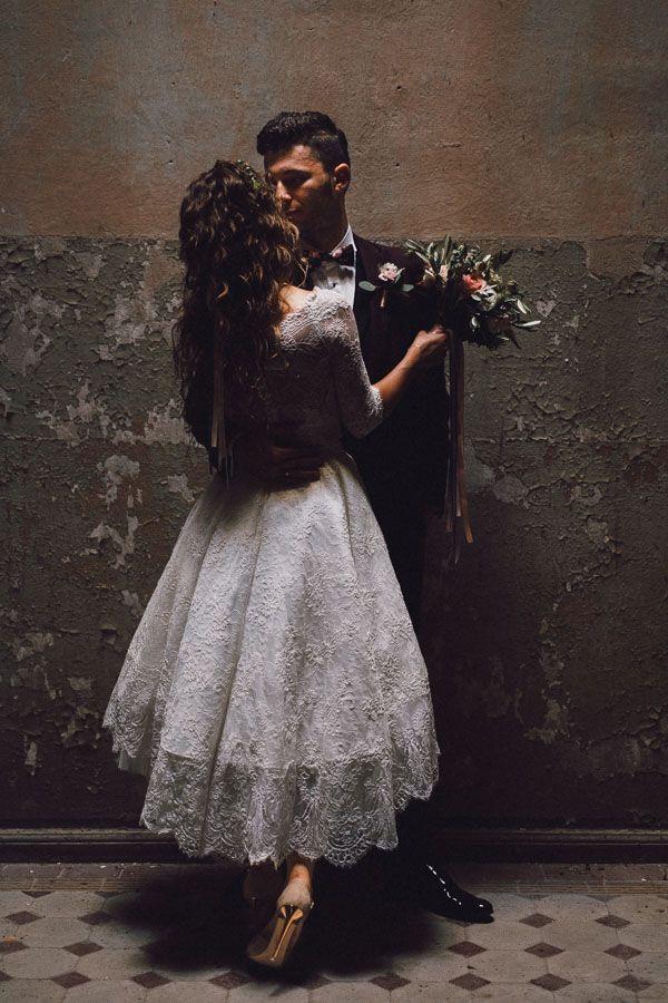 Pan młody obejmuje panią młodą, ona trzyma w rękach bukiet kwiatów