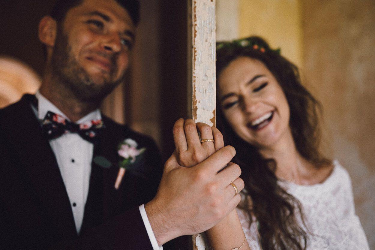 Pan młody dotyka dłoni żony, uśmiechają się