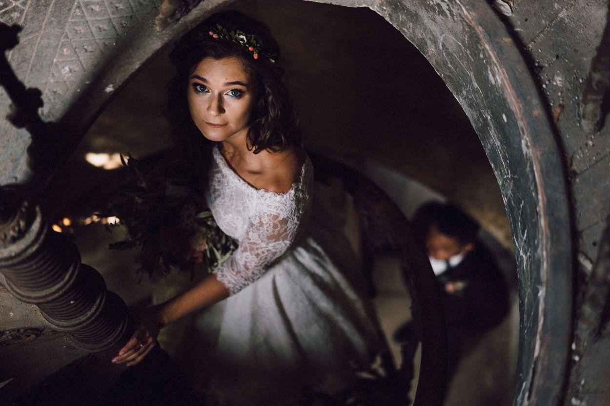 Pani młoda stoi na kręconych schodach w Pałacu Krowiarki