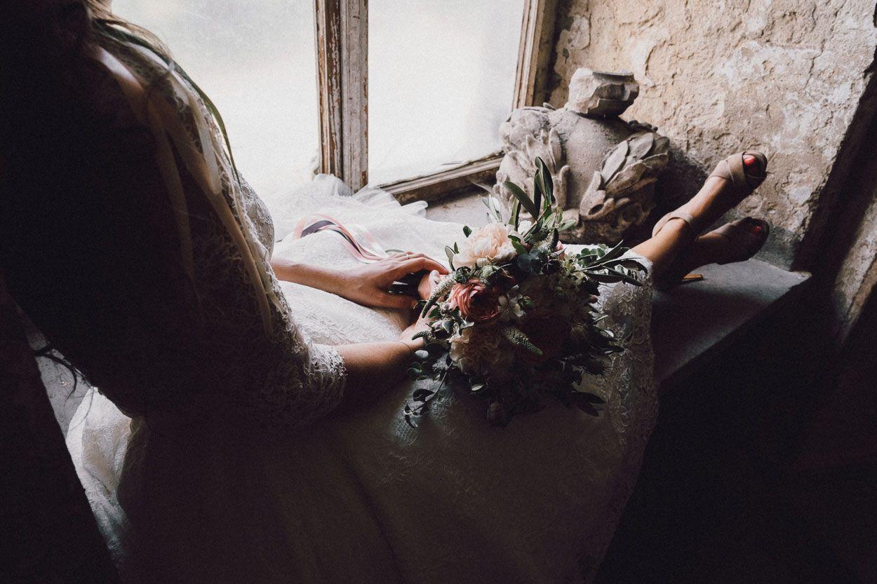 Pani młoda trzyma na kolanach bukiet kwiatów w Pałacu Krowiarki