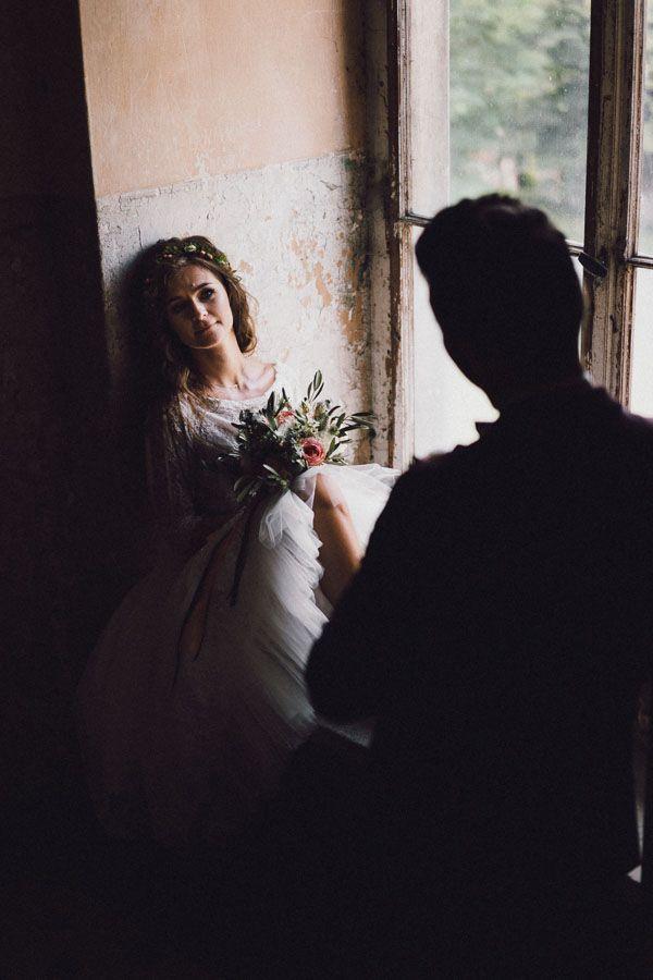 Pani młoda trzyma w ręce bukiet kwiatów i siedzi na parapecie patrząc na męża