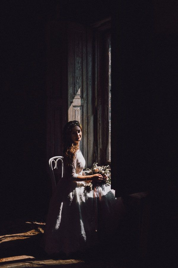Pani młoda siedzi przy oknie na krześle i trzyma w ręce bukiet kwiatów