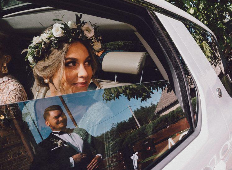 Pani młoda siedząca w samochodzie wygląda przez okno.