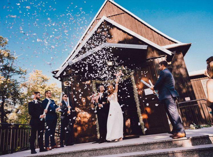 Para młoda wychodzi z kościoła, goście puszczają na nich białe konfetti