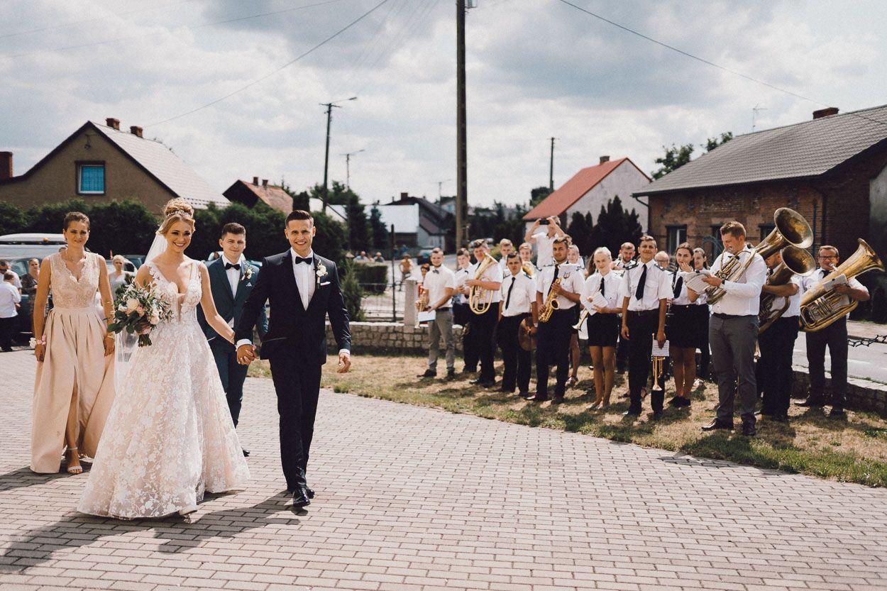 Dobry fotograf ślubny Para Młoda trzymając się za ręce idzie do Kościoła na ceremonię zaślubin, orkiestra gra