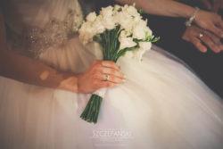 Detale ślubne Pani Młoda trzymająca bukiet kwiatów w kościele