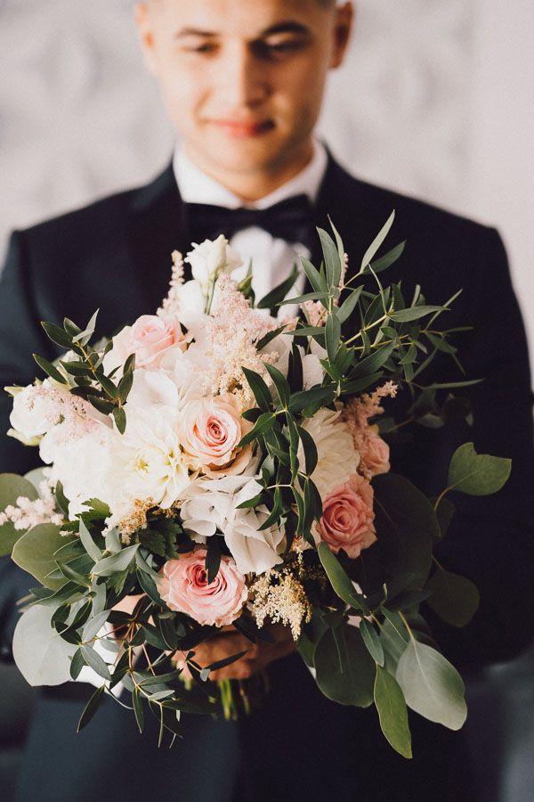 Pan młody trzyma w rękach bukiet ślubny