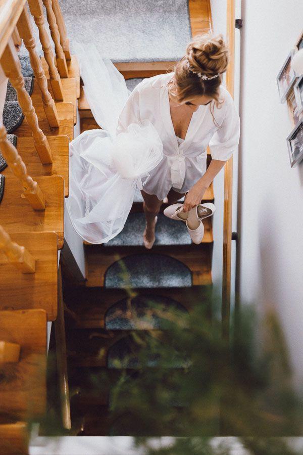 Pani młoda w szlafroku schodzi po schodach z suknią i butami