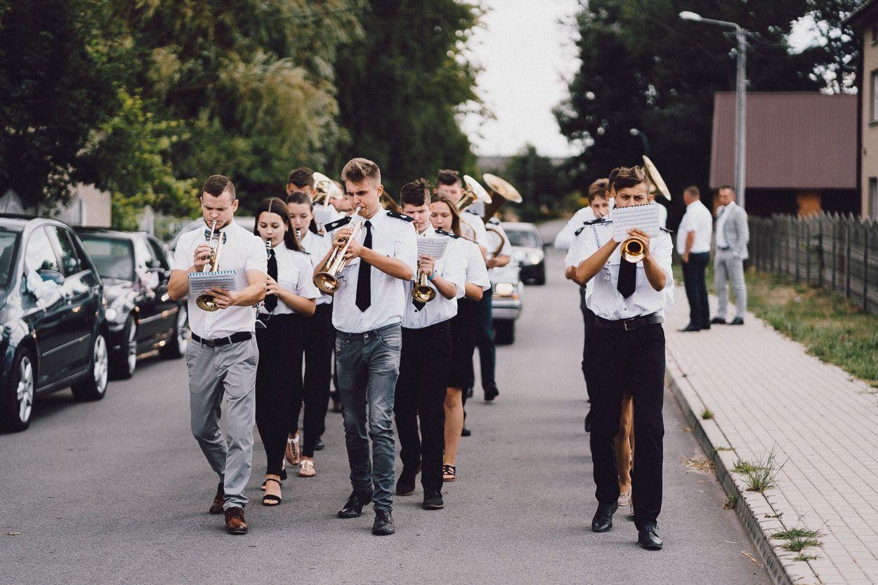 Orkiestra wprowadza samochód z Panem Młodym