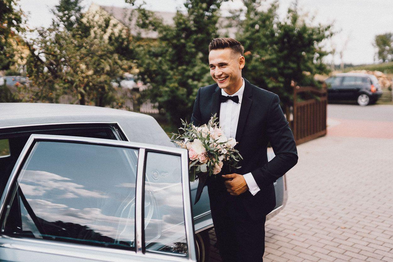 Pan Młody z bukietem kwiatów wysiada z samochodu