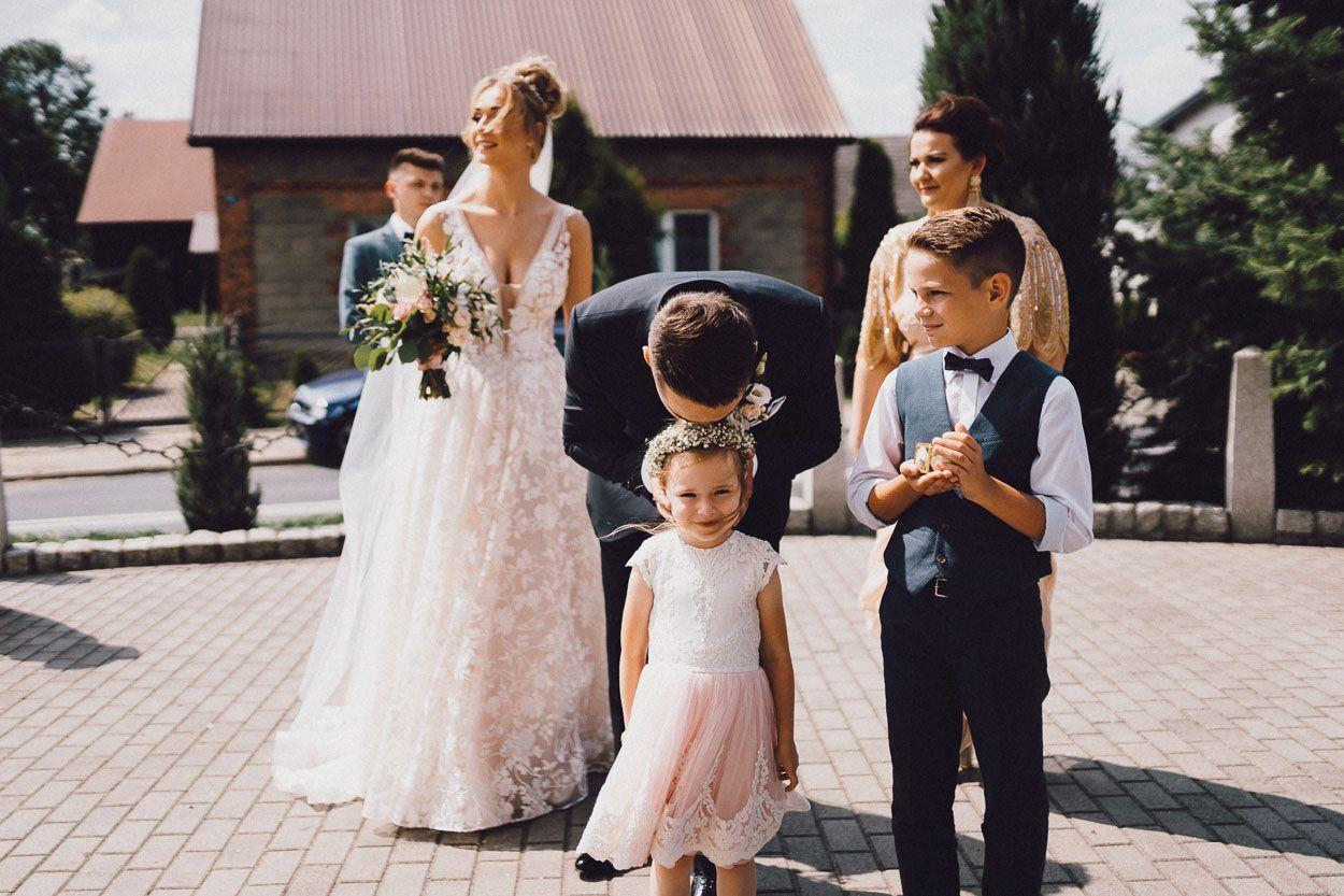 Pan Młody przed kościołem całuje małą dziewczynkę