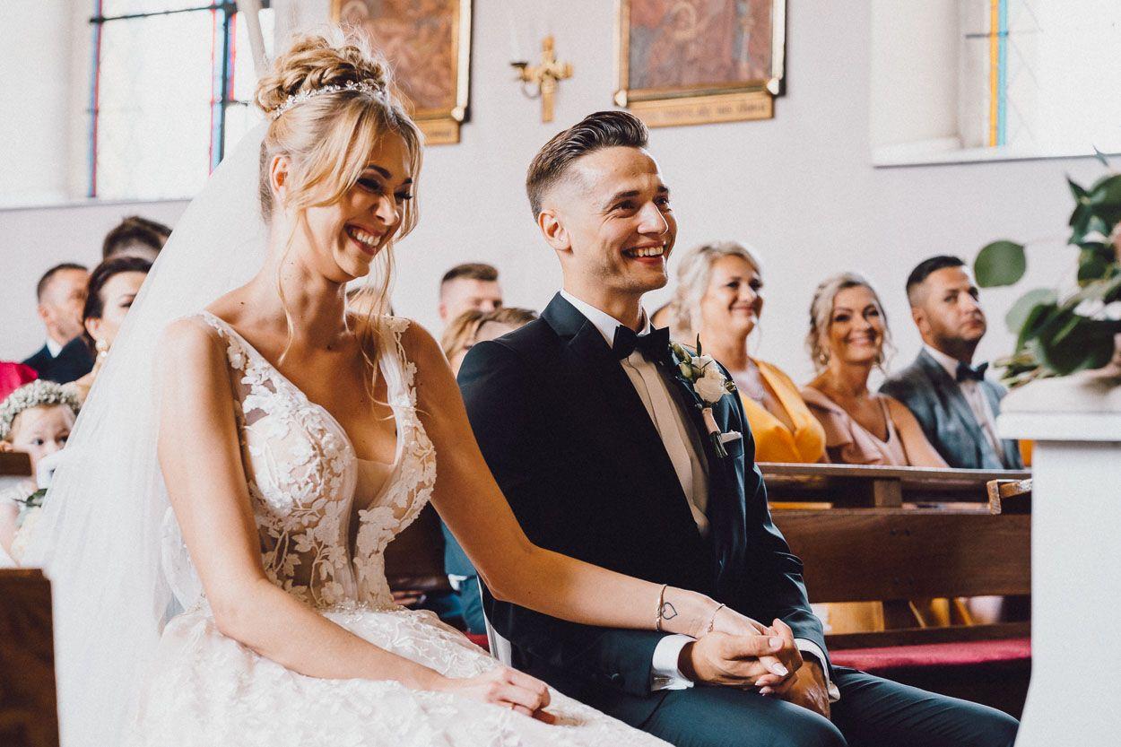 dobry fotograf ślubny Para Młoda trzyma się za ręce w kościele
