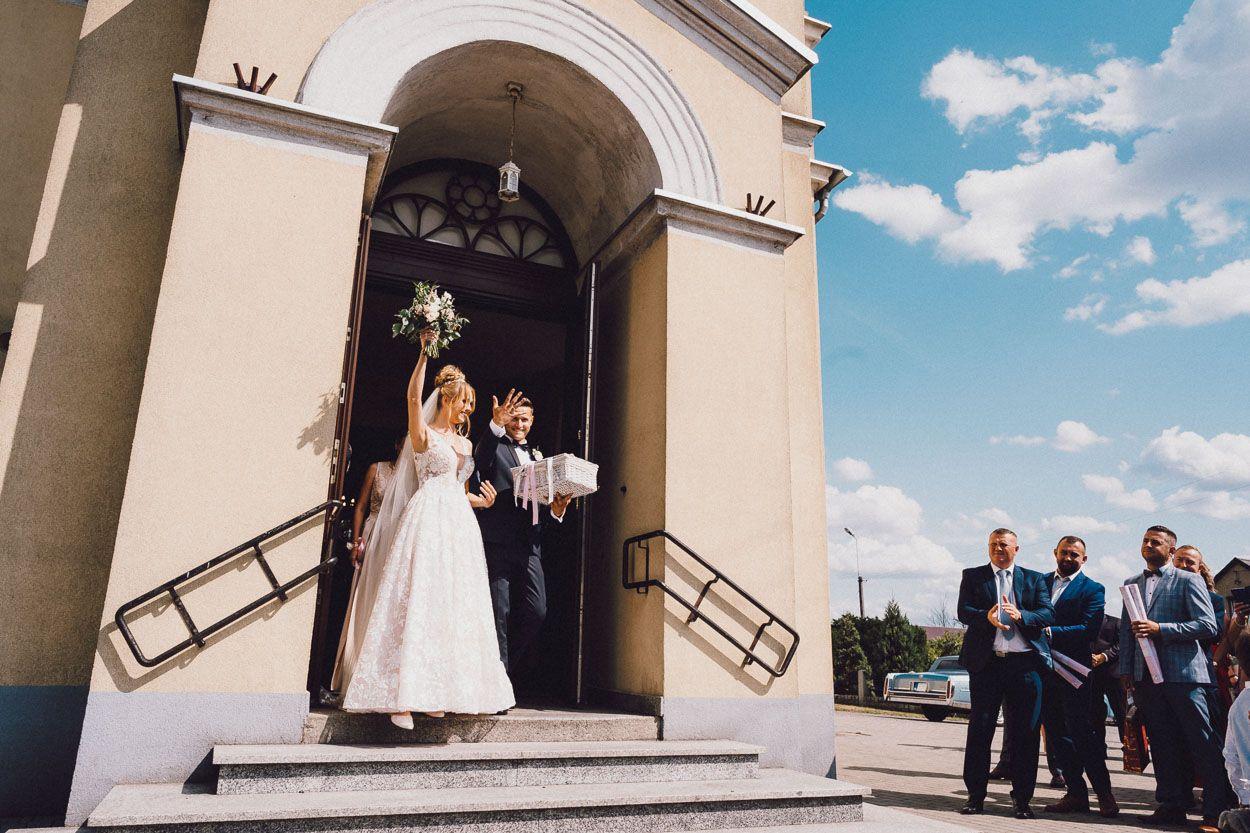 Pani Młoda unosi bukiet ślubny po zakończonej ceremonii zaślubin