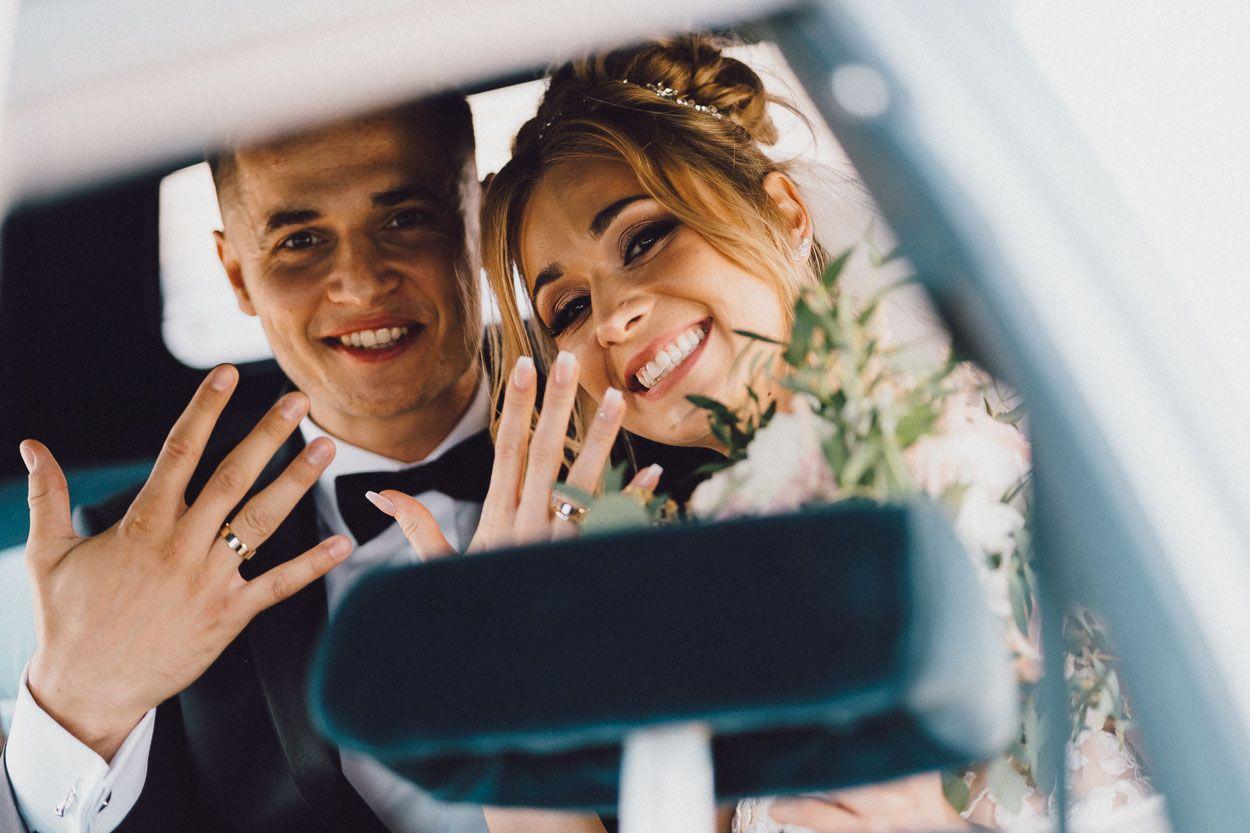 Para Młoda pokazuje obrączki podczas przejazdu dobry fotograf ślubny